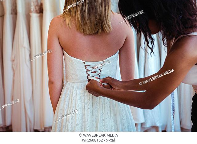Woman trying on wedding dress with the assistance of fashion designer