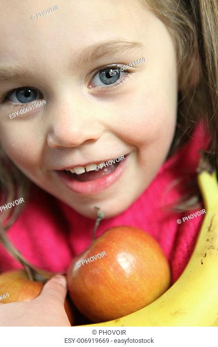 Little girl holding apples and banana