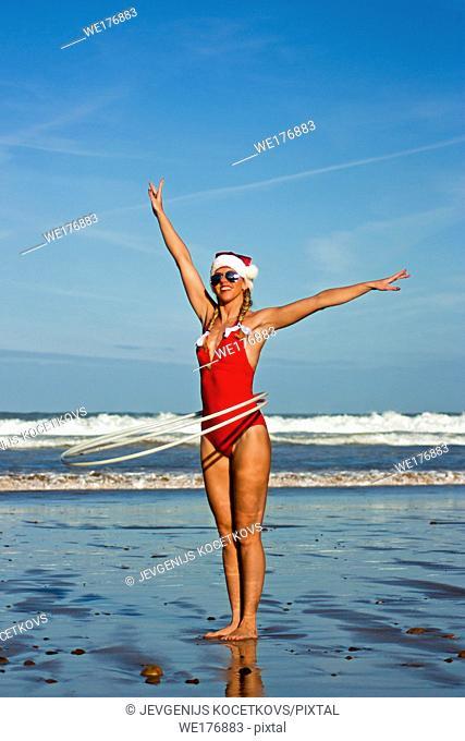Young girl in bikini and Christmas hat twirling hula hoop on the beach