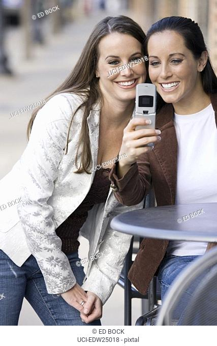 Two women sitting at cafÚ table taking picture of themselves