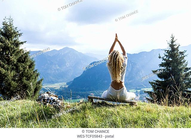 Germany, Bavaria, Oberammergau, young woman doing yoga on bench on mountain meadow