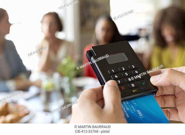 Close up waitress using credit card reader at cafe table