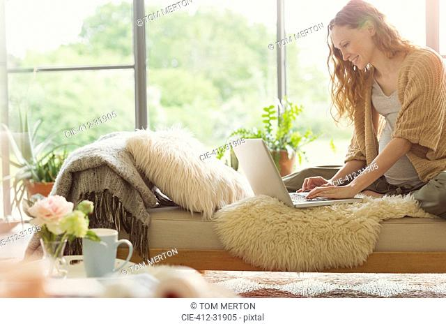 Pregnant woman using laptop on chaise lounge in living room