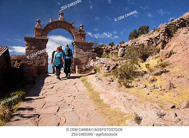 Tourists walking up the stairs to reach the town center passing through a gate, Taquile Island, Titicaca Lake, Puno Region, Peru, South America