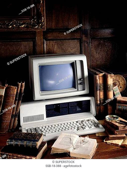 Desktop PC with books and eyeglasses on a table