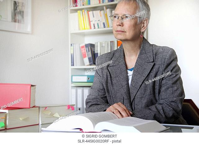 Lawyer reading text book in office