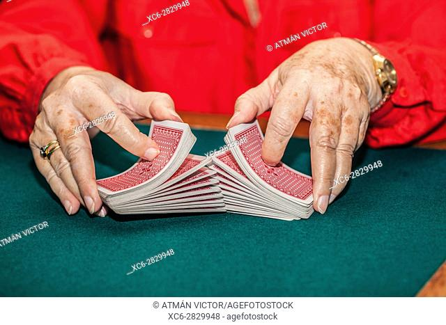 old woman shuffling canasta game cards