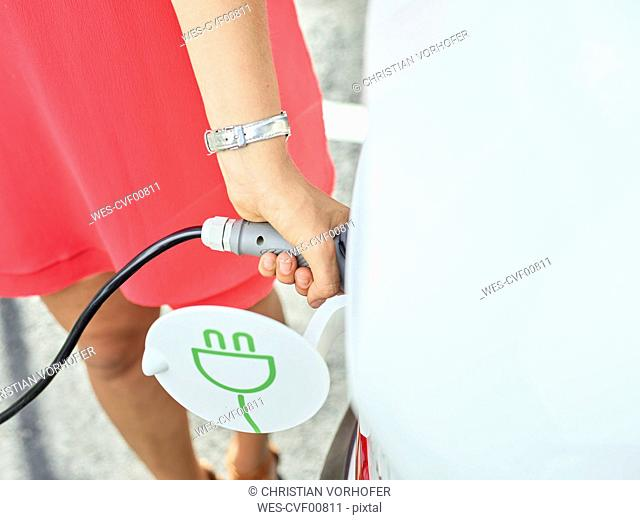 Close-up of woman charging electric car