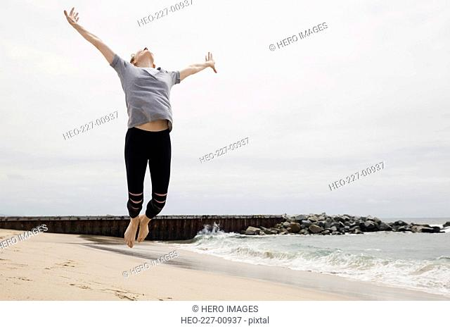 Exuberant woman jumping for joy on beach