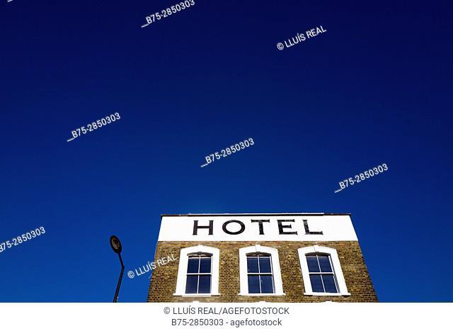 Cielo azul con la parte superior de un edificio y una farola apagada con el texto 'HOTEL'. Hampstead Village, London UK, Europa