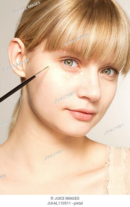 Portrait of young woman applying make up with brush