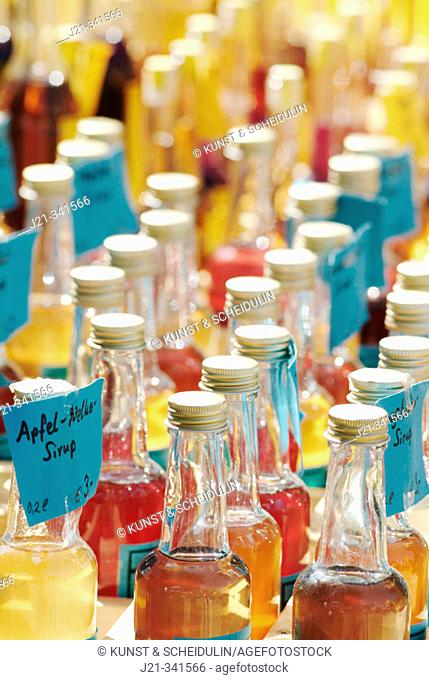 Small bottles with different home-made liqueurs on a market. Ratisbone. Upper Palatinate. Bavaria. Germany