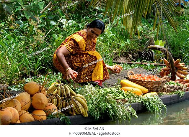 WOMAN BUYING VEGETABLES FROM LOCAL VEGETABLE SALESMAN IN COUNTRY BOAT, KUTTANAD, ALAPPUZHA