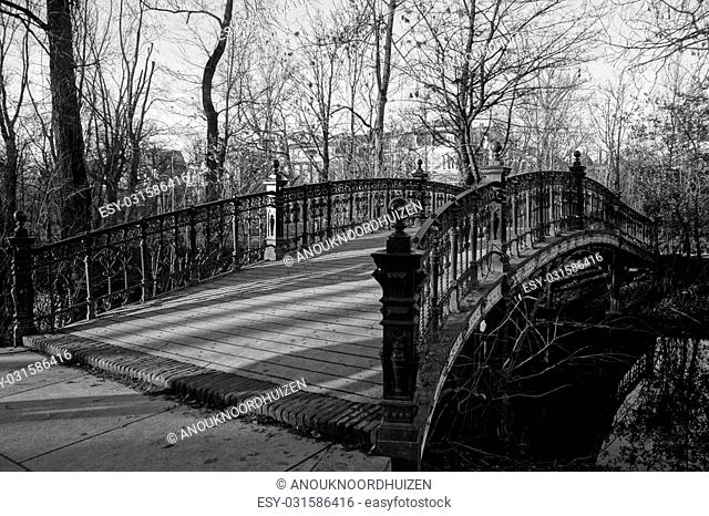 Black and white photo of an old bridge in a park