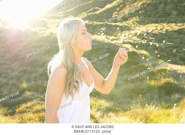 Caucasian woman blowing bubbles outdoors