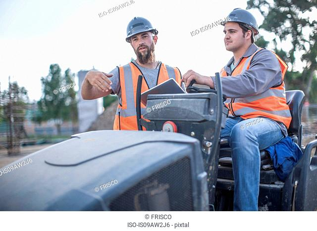Site manager explaining to steamroller driver on construction site