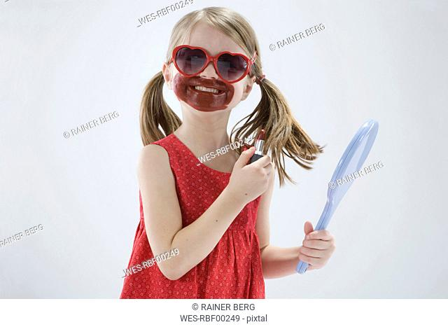 Girl 4-5 wearing sunglasses and playing with lipstick