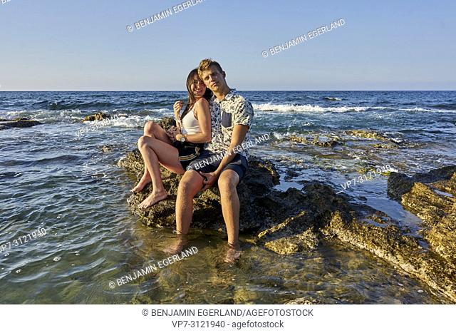 Couple sitting on rocks in sea, vacations, love. Chersonissos, Crete, Greece