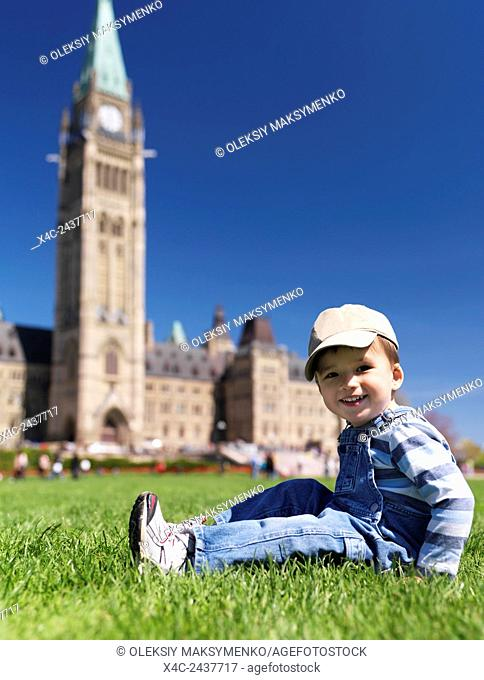Smiling child sitting on grass in front of The Parliament Building in Ottawa. Ontario, Canada springtime scenic