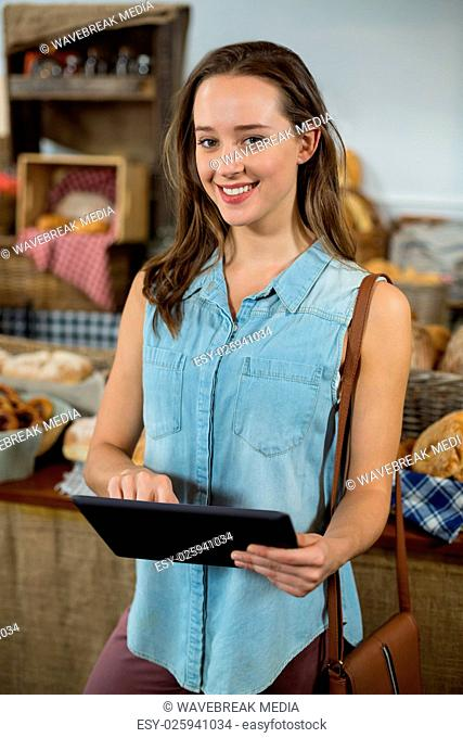 Portrait of smiling woman using digital tablet at counter