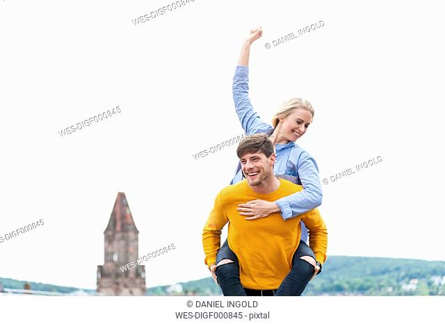 Happy young man carrying his girfriend piggyback