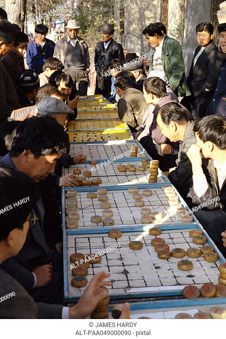 China, Xinjiang, Urumqi, line of people playing mah-jong outdoors