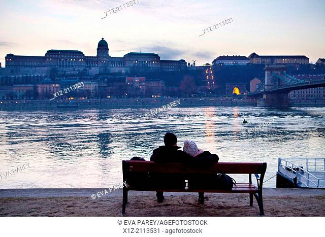 A couple rest in the shore of the Danube river, in front of the Royal Palace