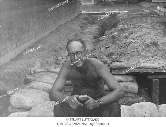 A candid photograph of a shirtless United States Army serviceman sitting down on a pile of sandbags, he is examining a object in his hands, Vietnam, 1967