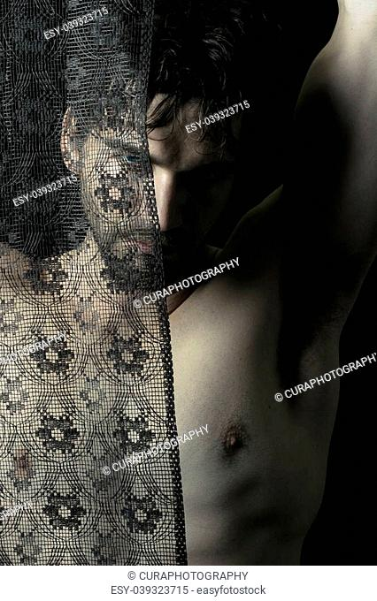 Portrait of beautiful young shirtless man behind black lace