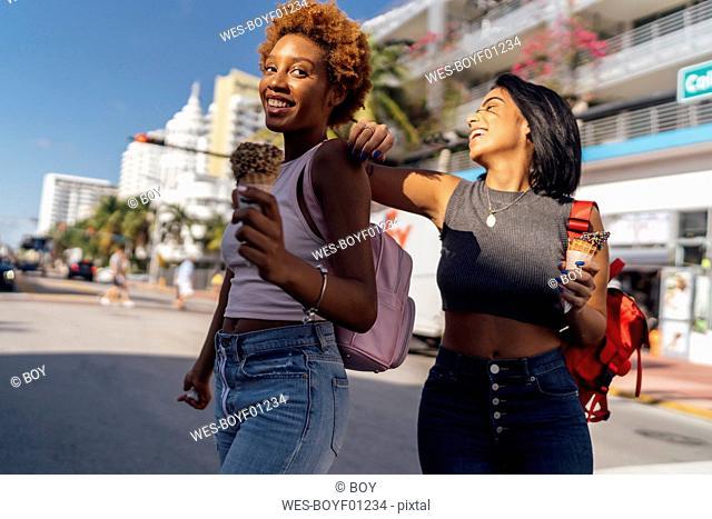 USA, Florida, Miami Beach, two happy female friends with ice cream cones in the city