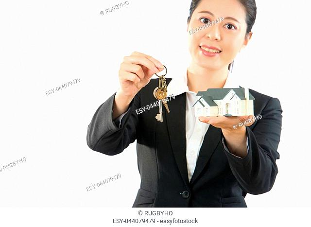 popular group manager looking for new franchisee. friendly smiling woman give house model and silver key on white wall background