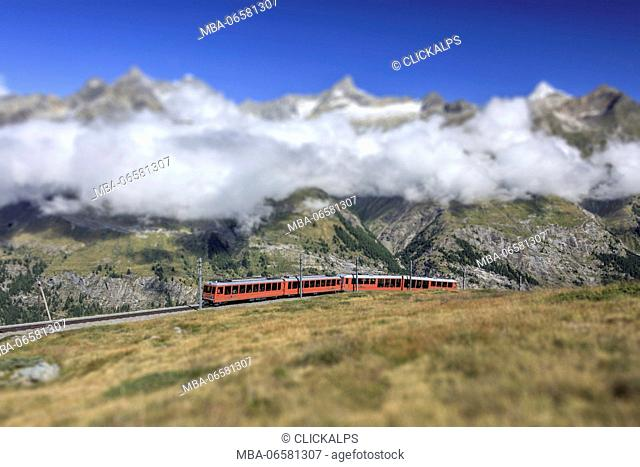 The Bahn train on its route with high peaks and mountain range in the background Gornergrat Canton of Valais Switzerland Europe