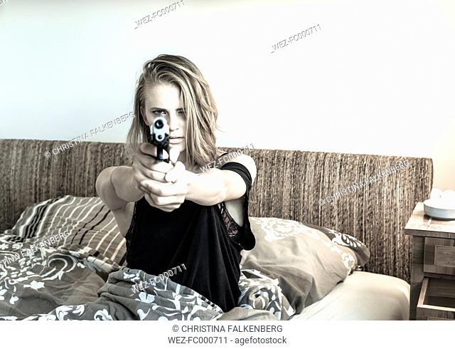 Woman sitting in her bed pointing a pistol at viewer