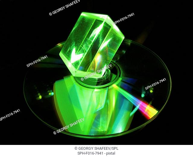 Glass prism and laser. Glass prism illuminated with green laser light, with a reflection seen in an optical disc. Compact discs (CDs) and digital versatile...