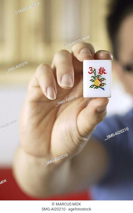 Close-up of hand holding mahjong tile with the Chinese script for Autumn