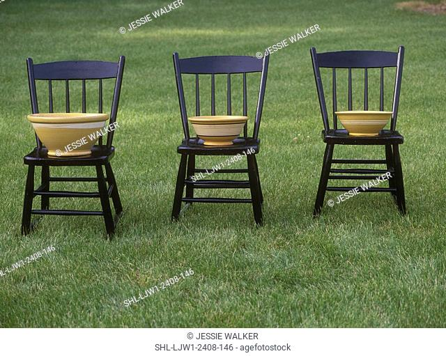 COLLECTIBLES: Three Wooden farm chairs on lawn. Collectible bowls yellowware on each chair, grass all around
