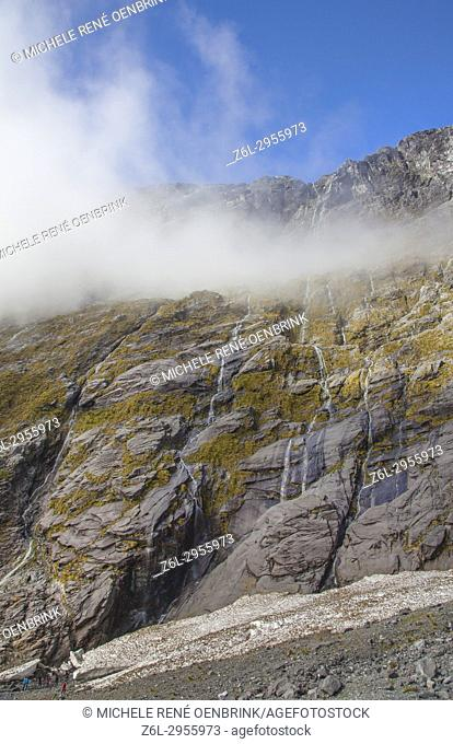 Waterfalls flowing down mountains from snowtops mountains in New Zealand