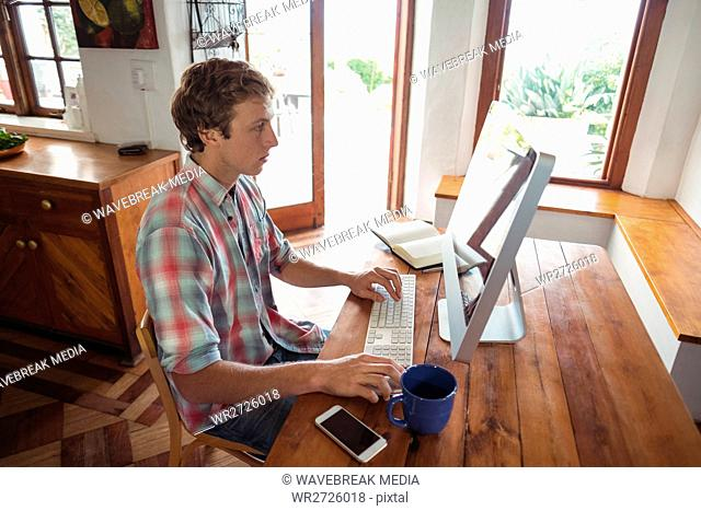 Man sitting at desk and working on computer