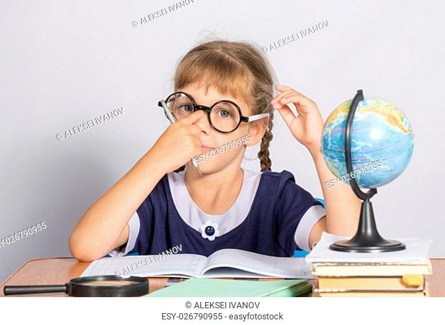 Schoolgirl corrects glasses while sitting at a desk in the classroom Geography