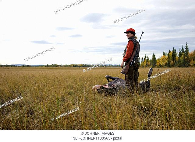 Woman with rifle standing beside dead body of red deer in swamp