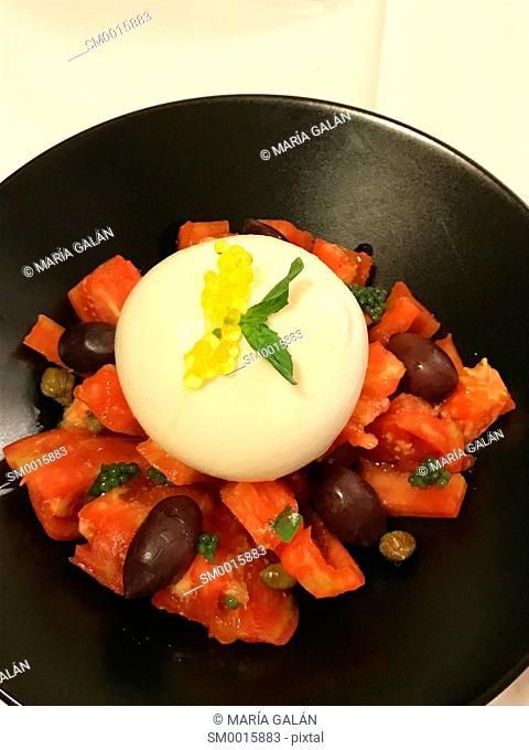 Tomato salad with black olives, cottage cheese and olive oil pearls