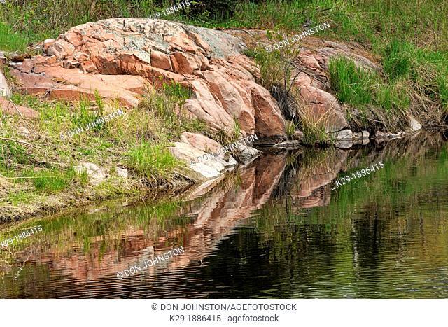 Canadian Shield granite outcrops reflected in a beaver pond, Killarney Provincial Park, Ontario, Canada