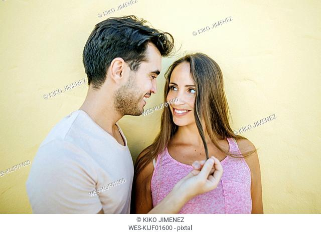 Young couple looking at each other in love against yellow wall