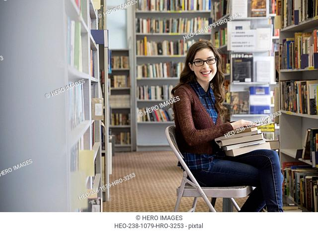 Portrait of bookstore worker with clipboard checking inventory