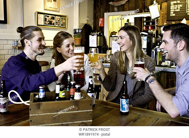 Friends toasting with beer in pub, Dorset, Bournemouth, England