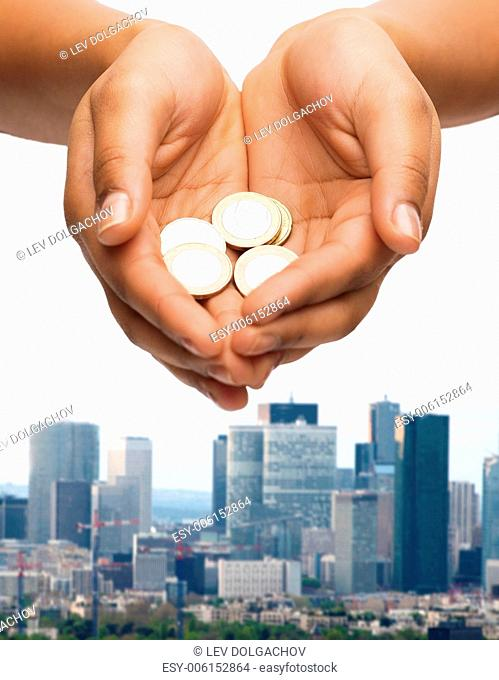 money and finances concept - close up of womans cupped hands showing euro coins