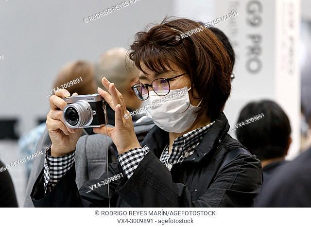 March 3, 2018, Yokohama, Japan - A woman tries out the new Lumix camera DC-GX7 MK3 at the CP+ Camera & Photo Imaging Show 2018 in Pacifico Yokohama