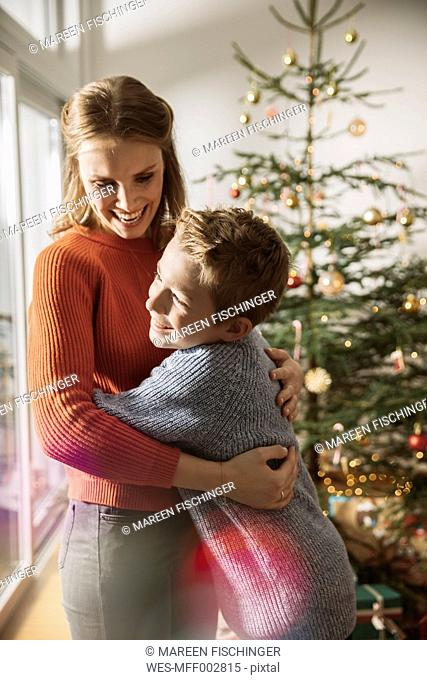 Happy mother and son hugging by Christmas tree