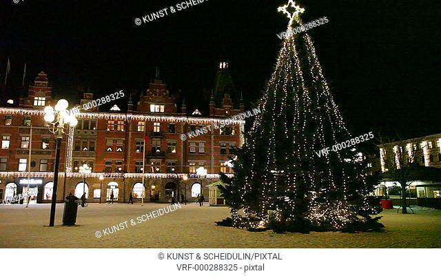 A large Christmas tree decorated with fairy lights is glittering on the square Stora Torget in the Swedish city Sundsvall at Christmas time