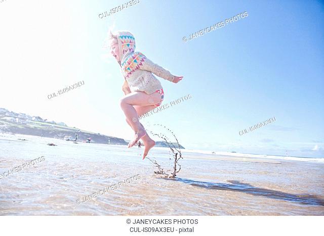 Girl jumping in water, Polzeath Beach, Cornwall